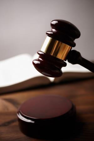 פטיש של שופט בדפיקה ברקע של ספר פתוח