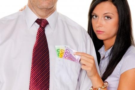 אשה מחזיקה שטרות בכיס חולצה של גבר