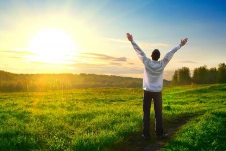איש עם ידיים פרושות כלפי מעלה בתחושת חופש
