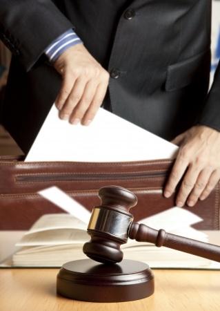 הוצאת פסק הדין מתוך המגרה של השולחן שעליו ספר פתוח ופטיש השופט