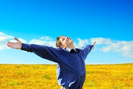 איש שמח מרים ידיים לשמים בשדה