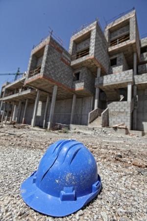 כובע של בנאי על רקע בנינים לא גמורים