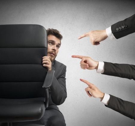 אצבעות מאשימות מונפות אל גבר המתחבא מאחורי כסא