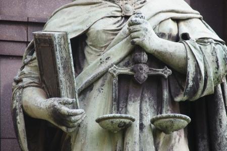 פסל של מאזניים וספר מוחזקים