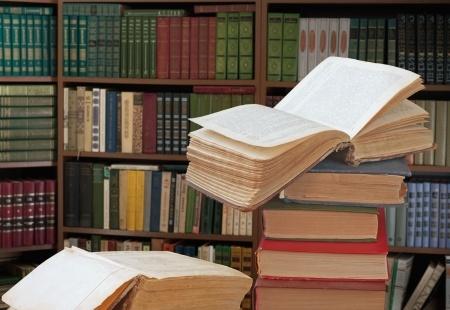 ספר פתוח על ערמת ספרים וברקע ספריה