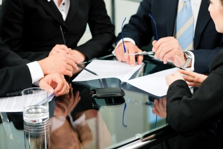אנשים יושבים על שולחן עם ניירות