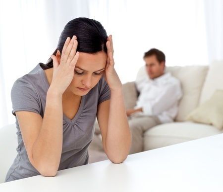 אשה מחזיקה את ראשה בתסכול כשגבר ברקע