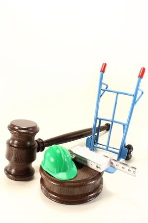 פטיש של שופט עם עגלה וכובע של בנאי