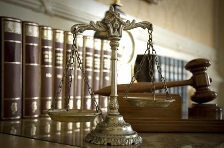 מאזניים ברקע ספרים עם פטיש של שופט