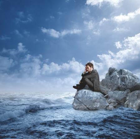 איש יושב על אבן בחוף ים