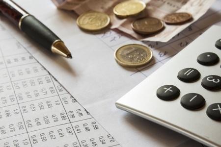 שולחם עמוס - כסף, עט מחשבון ומסמכים
