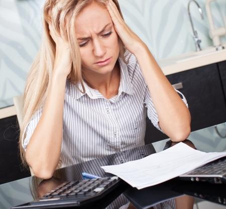 אשה יושבת מתוסכלת מול מסמכים ומחשבון
