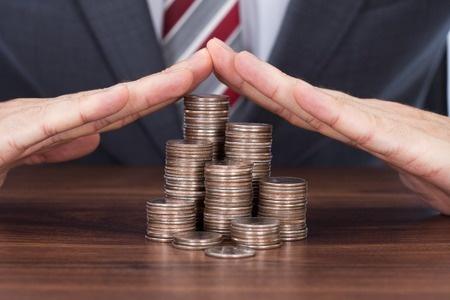 ידים בצורת גג על ערמות של מטבעות
