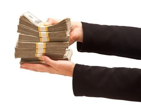 ידיים מחזיקות חבילות של שטרות של דולרים