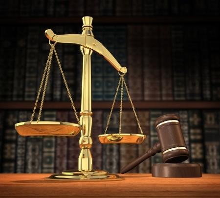 מאזניים ליד פטיש של שופט על רקע ספרייה