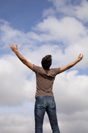 איש עומד עם ידיים פרושות כלפי השמים